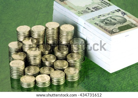 Stack of Indian rupee coins and notes - stock photo