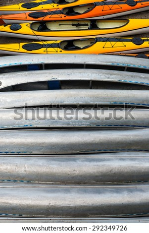Stack of 13 kayaks nex to each other. - stock photo
