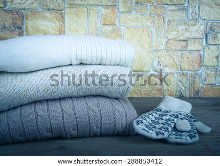 Stack of knitting clothes and painted mittens on wooden table opposite a stony wall. Toned.