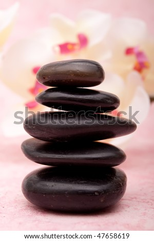 Stack of lastone therapy rocks in front of an orchid