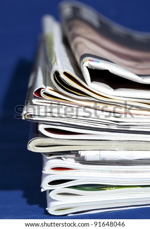 stack of magazines isolated on blue - stock photo