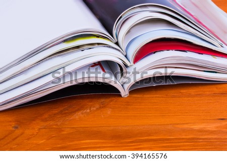 Stack of magazines on a wooden background