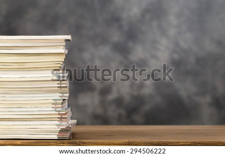 Stack of magazines on left side of table with copy space - stock photo