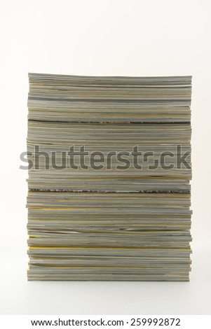 Stack of magazines showing ends of pages - neutral colours- against white background