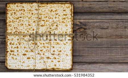 Stack of matzah or matza on a vintage wood background presented as a gift with copy space. Perfect for your Passover design.