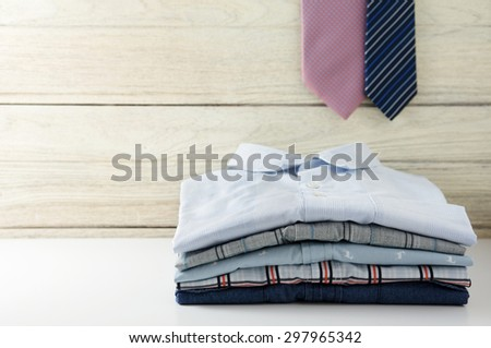 Stack of men shirts and tie hanging with white wooden background - stock photo
