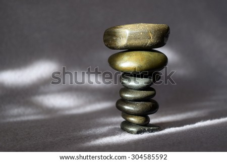 Stack of mismatched smooth and jagged stones balancing perfectly anyway - stock photo
