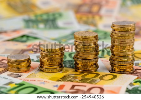 stack of money coins rising curve, symbolic photo for increasing profits and rising costs - stock photo