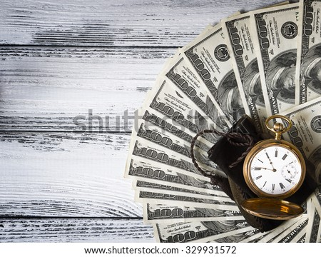 Stack of money dollars laid out like a fan with antique gold watch on white retro stylized wood background with vignetting effect - stock photo