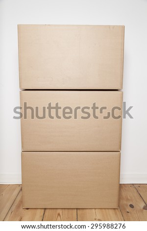 stack of moving boxes on wooden floor - stock photo