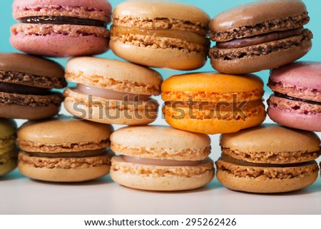 Stack of multi-colored macarons over pastel blue background - stock photo