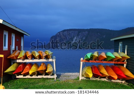Stack of multicolored kayaks on the shore in Newfoundland, Canada - stock photo