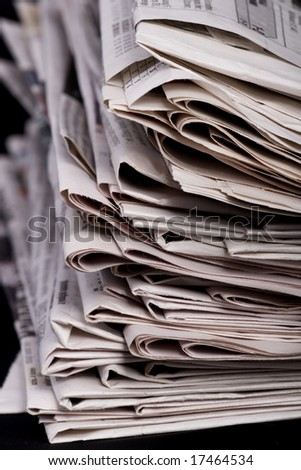 Stack of newspaper on black background close up