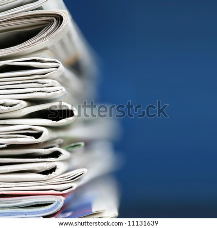 Stack of newspaper on blue background close up - stock photo