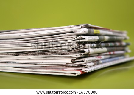 stack of newspaper on green background close up - stock photo