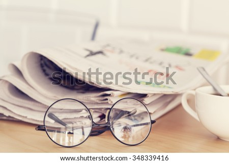 Stack of newspapers, eyeglasses on table - stock photo