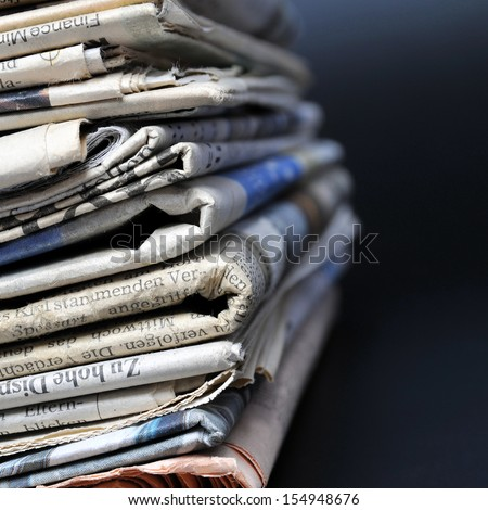 Stack of newspapers on black background - stock photo