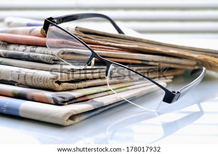 Stack of newspapers on office desk with glasses. - stock photo