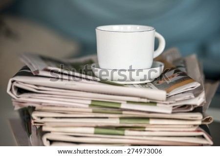 Stack of newspapers with a cup of coffee - stock photo
