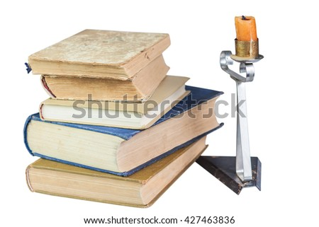 Stack of old books and a candle isolated on white background