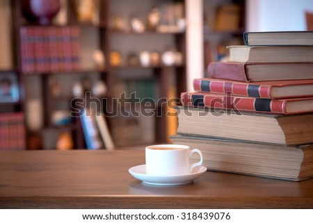 Stack of old books and tablet over wooden table