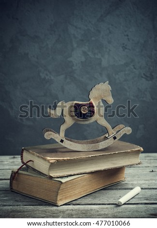 Stack of old books and wooden toy horse on concrete background. Chalk and wooden table vintage still life. Back to school composition.