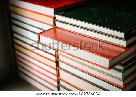 Stack of old books in shelf - stock photo
