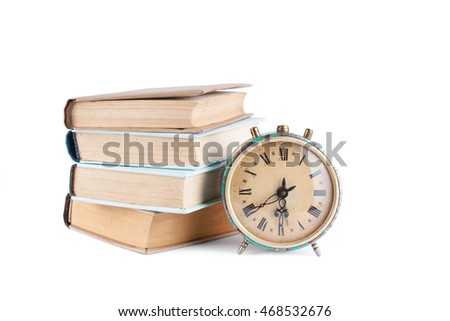 Stack of old books with clock isolated on white background