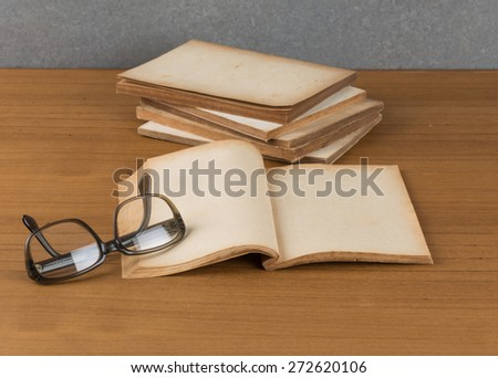 stack of old books with glasses - stock photo
