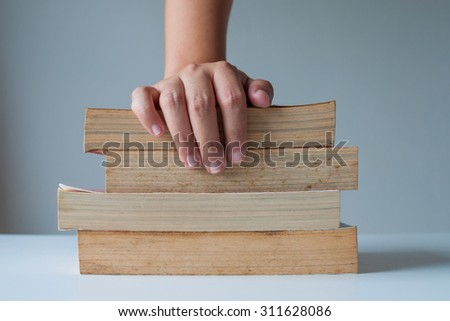 Stack of old books with hand catching. - stock photo