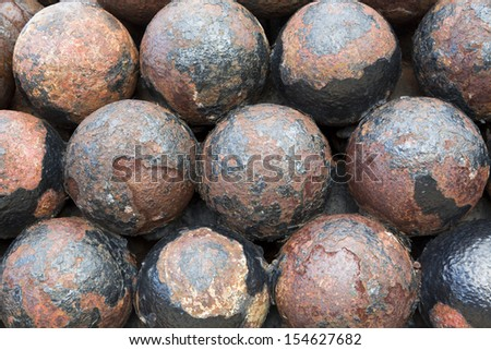 stack of old colonial rusty cannon balls - stock photo