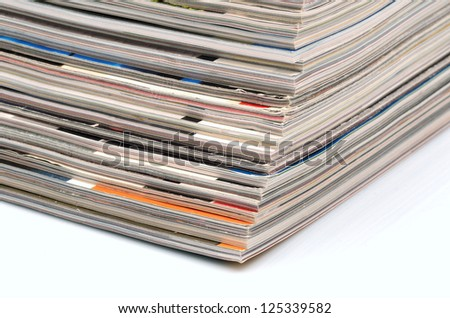 Stack of old colored magazines on white background