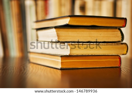 Stack of old hardcover books on a wooden surface against a row of books on a bookshelf in a library,school, office or home with shallow dof
