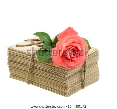 Stack of old love letters and postcards with pink rose flower isolated on white background. Nostalgic sentimental picture - stock photo