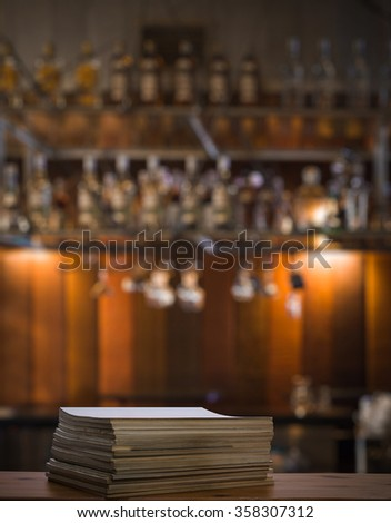 stack of old magazines on wooden table in a night club