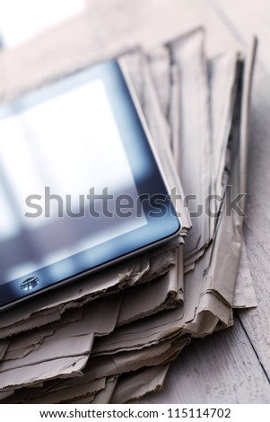 Stack of old newspapers and a tablet pc on the wooden table - stock photo