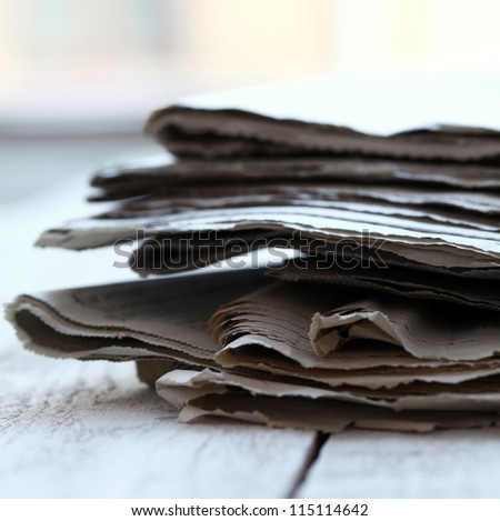 Stack of old newspapers on wooden table