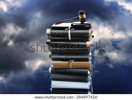 Stack of old paper folders and gavel on sky  - stock photo