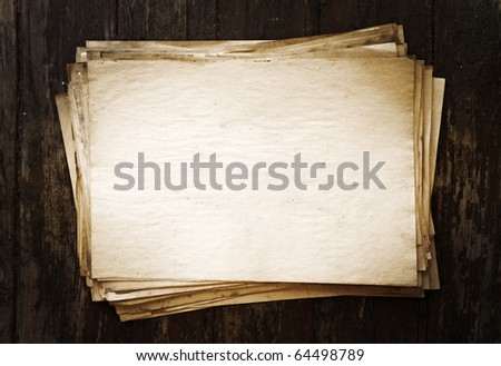 stack of old papers on wooden background - stock photo