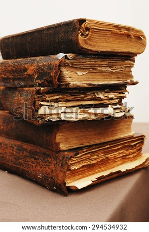 stack of old tattered books on the table - stock photo