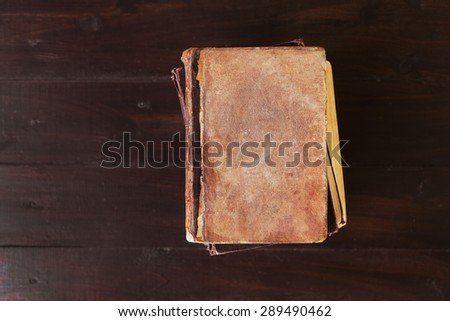 Stack of old vintage books on brown wood background, theme of the reading and education, selective focus and shallow dof - stock photo