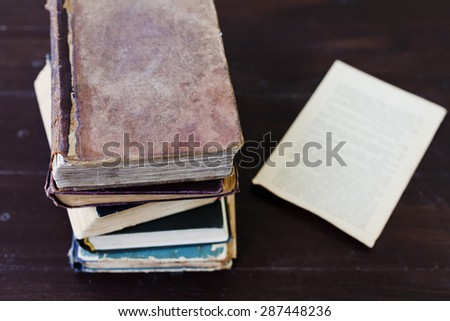 Stack of old vintage books on dark wood background, selective focus and shallow dof - stock photo