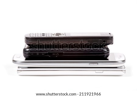 Stack of older model cell phones and smartphones isolated on white - stock photo