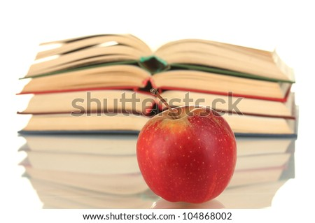 stack of open books with apple on white background close-up