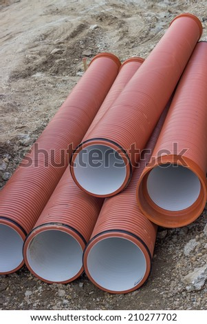 Stack of orange underground plastic pipes at construction site - stock photo