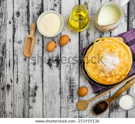 stack of pancakes and ingredients on a wooden background - stock photo