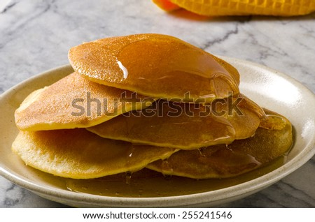 Stack of pancakes in a plate with syrup. Focus on foreground. - stock photo