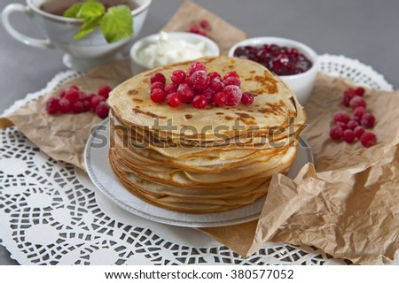 Stack of pancakes served with fresh cranberries, sour cream and jam.  - stock photo