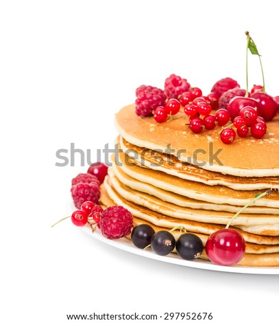 Stack of pancakes with berries on a plate isolated on white background