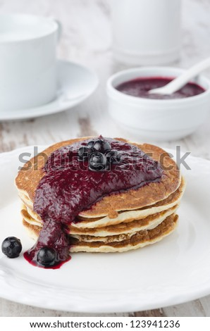 stack of pancakes with black currant jam on a white plate, a bowl of jam in the background - stock photo